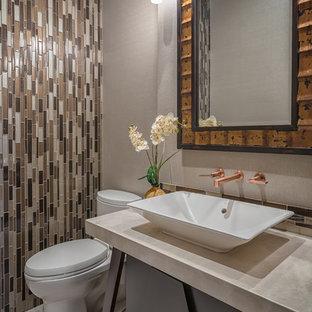 Kleine Tropenstil Gästetoilette mit offenen Schränken, dunklen Holzschränken, Wandtoilette mit Spülkasten, beigefarbenen Fliesen, Glasfliesen, beiger Wandfarbe, Travertin, Aufsatzwaschbecken und Quarzwerkstein-Waschtisch in San Diego