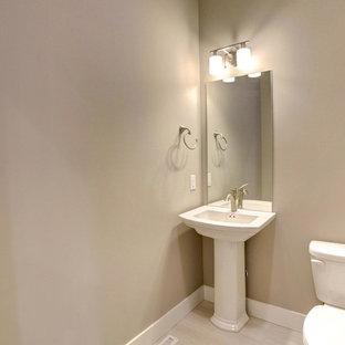 Свежая идея для дизайна: туалет среднего размера в современном стиле с раздельным унитазом, бежевыми стенами, полом из ламината, раковиной с пьедесталом и бежевым полом - отличное фото интерьера