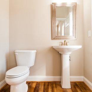 Diseño de aseo de estilo americano, pequeño, con sanitario de dos piezas, paredes beige, suelo de madera oscura, lavabo con pedestal y suelo marrón