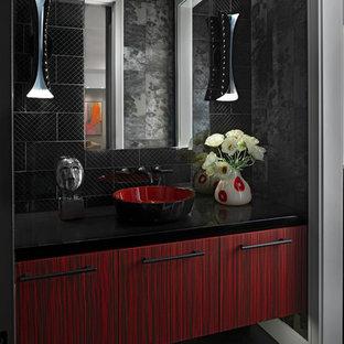 Foto på ett funkis svart badrum, med släta luckor, röda skåp, ett fristående handfat, svart golv, svart kakel och svarta väggar