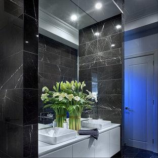 Стильный дизайн: большой туалет в стиле модернизм с белыми фасадами, черными стенами, черной плиткой, керамогранитной плиткой, полом из керамогранита, фасадами с филенкой типа жалюзи, настольной раковиной, столешницей из кварцита, черным полом и белой столешницей - последний тренд