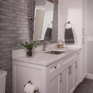 Immagine di un bagno di servizio stile americano di medie dimensioni con ante in stile shaker, ante bianche, WC a due pezzi, piastrelle grigie, piastrelle di vetro, pareti grigie, pavimento in gres porcellanato, lavabo sottopiano, top in quarzo composito, pavimento grigio e top bianco