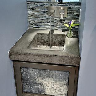 Cette photo montre un petit WC et toilettes tendance avec un placard à porte plane, des portes de placard grises, un WC séparé, un carrelage noir, un carrelage bleu, un carrelage gris, un carrelage blanc, des carreaux en allumettes, un mur bleu, un sol en carrelage de porcelaine, un lavabo intégré, un plan de toilette en béton, un sol multicolore et un plan de toilette gris.