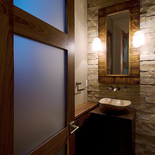 Powder room - small contemporary beige tile and stone tile powder room idea in Denver with a vessel sink, wood countertops, a two-piece toilet, beige walls and brown countertops