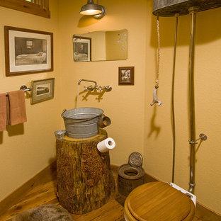 Kleine Rustikale Gästetoilette mit hellbraunen Holzschränken, Toilette mit Aufsatzspülkasten, gelber Wandfarbe, dunklem Holzboden und Aufsatzwaschbecken in Denver