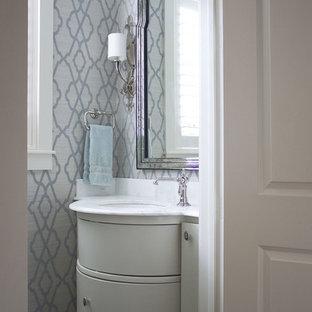 Réalisation d'un petit WC et toilettes tradition avec un lavabo encastré, un placard en trompe-l'oeil, des portes de placard blanches, un plan de toilette en marbre, béton au sol, un carrelage blanc, un mur multicolore et un plan de toilette blanc.