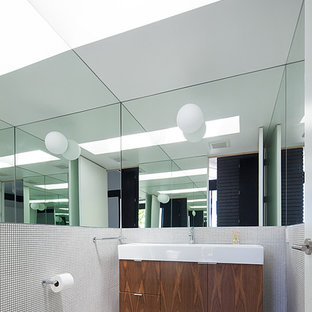 Small midcentury cloakroom in Los Angeles with flat-panel cabinets, medium wood cabinets, a two-piece toilet, a submerged sink, multi-coloured tiles, mosaic tiles, concrete flooring and beige floors.