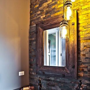 シカゴの小さいラスティックスタイルのおしゃれなトイレ・洗面所 (落し込みパネル扉のキャビネット、濃色木目調キャビネット、茶色いタイル、石タイル、ベージュの壁、ベッセル式洗面器) の写真