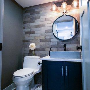バンクーバーのインダストリアルスタイルのおしゃれなトイレ・洗面所 (黒いキャビネット、グレーの壁、ベッセル式洗面器、クオーツストーンの洗面台、造り付け洗面台、レンガ壁) の写真
