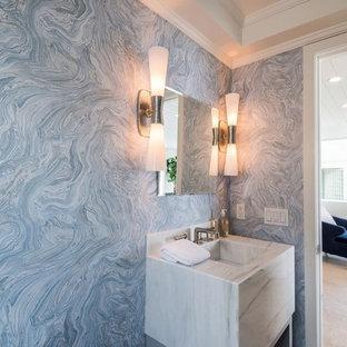 Стильный дизайн: маленький туалет в морском стиле с синей плиткой, синими стенами, светлым паркетным полом, раковиной с несколькими смесителями, мраморной столешницей, бежевым полом и белой столешницей - последний тренд