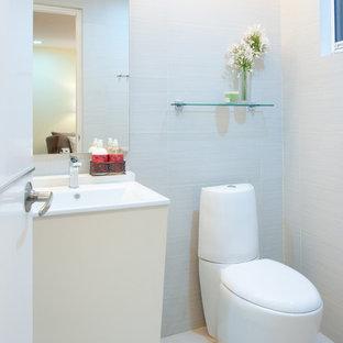 Idée de décoration pour un WC et toilettes design avec un lavabo intégré, un placard à porte plane, des portes de placard beiges, un WC séparé et un carrelage gris.