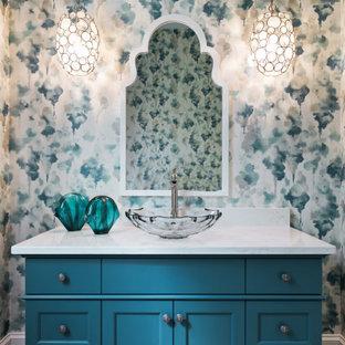 Foto på ett mellanstort maritimt vit toalett, med luckor med infälld panel, turkosa skåp, en toalettstol med separat cisternkåpa, flerfärgade väggar, klinkergolv i porslin, ett fristående handfat, bänkskiva i kvarts och brunt golv