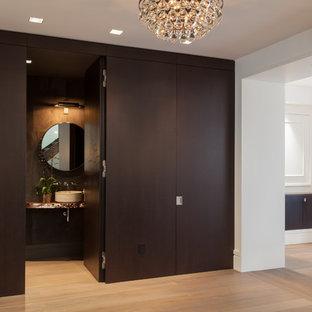 Diseño de aseo contemporáneo, pequeño, con armarios tipo mueble, puertas de armario negras, baldosas y/o azulejos grises, baldosas y/o azulejos de cemento, paredes grises, suelo de madera clara, lavabo sobreencimera y encimera de cobre