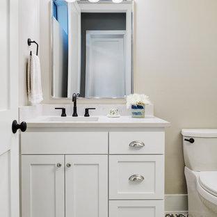 Неиссякаемый источник вдохновения для домашнего уюта: туалет среднего размера в стиле кантри с фасадами в стиле шейкер, белыми фасадами, унитазом-моноблоком, серыми стенами, полом из цементной плитки, врезной раковиной, столешницей из искусственного кварца, черным полом и белой столешницей