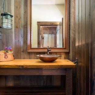 Bild på ett mellanstort rustikt orange oranget toalett, med möbel-liknande, bruna skåp, en toalettstol med separat cisternkåpa, brun kakel, bruna väggar, skiffergolv, träbänkskiva, grönt golv och ett fristående handfat