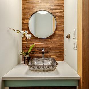 Mittelgroße Retro Gästetoilette mit verzierten Schränken, türkisfarbenen Schränken, Wandtoilette mit Spülkasten, braunen Fliesen, Stäbchenfliesen, weißer Wandfarbe, braunem Holzboden, Aufsatzwaschbecken, braunem Boden und Quarzwerkstein-Waschtisch in Calgary