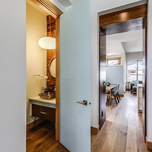 Medium sized retro cloakroom in Calgary with flat-panel cabinets, dark wood cabinets, a two-piece toilet, multi-coloured tiles, brown walls, medium hardwood flooring, a vessel sink, brown floors and engineered stone worktops.