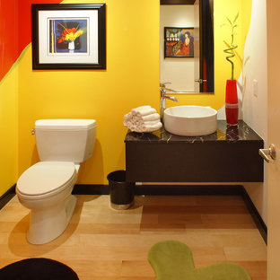 Modelo de aseo contemporáneo, de tamaño medio, con armarios con paneles lisos, puertas de armario negras, sanitario de dos piezas, baldosas y/o azulejos amarillos, suelo de madera clara, lavabo sobreencimera, encimera de mármol, suelo amarillo y encimeras negras