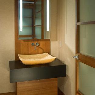 Ejemplo de aseo asiático, de tamaño medio, con armarios con paneles lisos, puertas de armario de madera oscura, lavabo sobreencimera, paredes beige, suelo de madera en tonos medios y suelo marrón