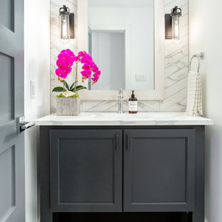 Пример оригинального дизайна: туалет среднего размера в морском стиле с фасадами в стиле шейкер, серыми фасадами, белыми стенами, врезной раковиной, белым полом и белой столешницей