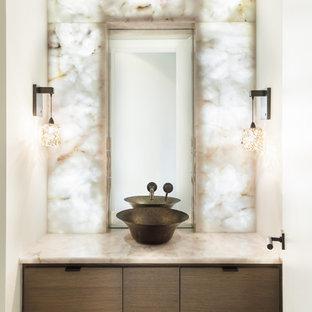 Идея дизайна: туалет в современном стиле с настольной раковиной, плоскими фасадами, темными деревянными фасадами, белой плиткой, плиткой из листового камня, белыми стенами и бежевой столешницей