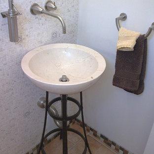 Imagen de aseo contemporáneo, de tamaño medio, con armarios abiertos, baldosas y/o azulejos beige, baldosas y/o azulejos en mosaico, paredes grises, suelo de travertino, lavabo con pedestal y suelo beige