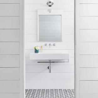 Kleine Landhaus Gästetoilette mit weißen Schränken, weißer Wandfarbe, Keramikboden, Wandwaschbecken, schwarzem Boden, weißer Waschtischplatte, schwebendem Waschtisch, Holzdecke und Wandpaneelen in Austin