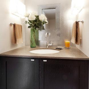 Idee per un bagno di servizio design di medie dimensioni con lavabo sottopiano, ante in stile shaker, ante in legno bruno, top in pietra calcarea, WC monopezzo, pareti bianche e pavimento in cemento