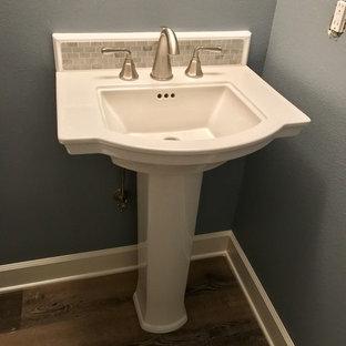 Свежая идея для дизайна: маленький туалет в классическом стиле с раздельным унитазом, белой плиткой, мраморной плиткой, синими стенами, полом из ламината, раковиной с пьедесталом и разноцветным полом - отличное фото интерьера