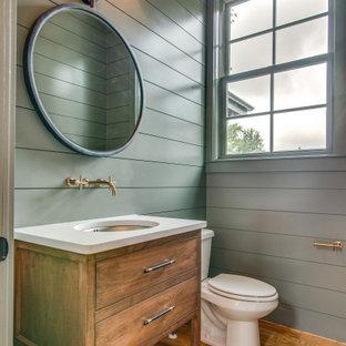 Стильный дизайн: туалет среднего размера в стиле современная классика с плоскими фасадами, фасадами цвета дерева среднего тона, раздельным унитазом, зелеными стенами, светлым паркетным полом, врезной раковиной, столешницей из искусственного кварца и белой столешницей - последний тренд