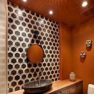 Cette image montre un petit WC et toilettes bohème avec une vasque, un placard à porte shaker, un plan de toilette en bois, des carreaux de céramique, un mur orange, un carrelage noir et blanc, des portes de placard en bois sombre, un WC à poser et un plan de toilette marron.