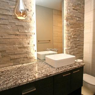 Mittelgroße Moderne Gästetoilette mit Aufsatzwaschbecken, flächenbündigen Schrankfronten, schwarzen Schränken, Granit-Waschbecken/Waschtisch, Toilette mit Aufsatzspülkasten, grauen Fliesen, Steinfliesen, grauer Wandfarbe und Porzellan-Bodenfliesen in Seattle
