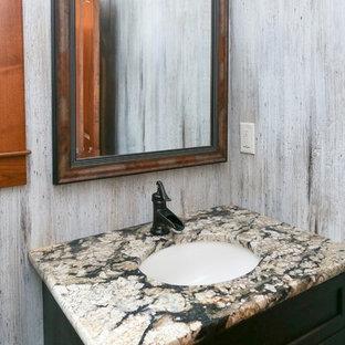 他の地域の中サイズのラスティックスタイルのおしゃれなトイレ・洗面所 (黒いキャビネット、グレーのタイル、グレーの壁、アンダーカウンター洗面器、御影石の洗面台、マルチカラーの洗面カウンター) の写真