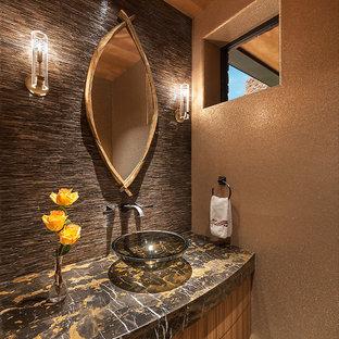 Idées déco pour un grand WC et toilettes sud-ouest américain avec des portes de placard en bois brun, une vasque, un placard en trompe-l'oeil, un carrelage marron, un carrelage de pierre, un sol en marbre et un plan de toilette en marbre.