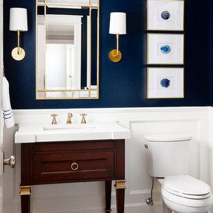 Foto på ett litet vintage vit toalett, med möbel-liknande, skåp i mörkt trä, en toalettstol med separat cisternkåpa, blå väggar, ett undermonterad handfat, grått golv, klinkergolv i porslin och marmorbänkskiva