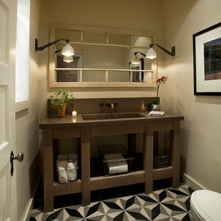 Example of a classic powder room design in Phoenix with an integrated sink, open cabinets, dark wood cabinets, beige walls and brown countertops