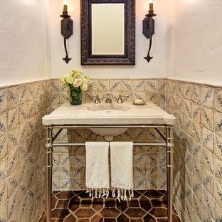 Idées déco pour un petit WC et toilettes méditerranéen avec un plan vasque, un carrelage beige, un carrelage marron, des carreaux de céramique, un mur blanc, un sol en carreau de terre cuite et un plan de toilette beige.