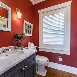 タンパのトラディショナルスタイルのおしゃれなトイレ・洗面所 (落し込みパネル扉のキャビネット、黒いキャビネット、赤い壁、無垢フローリング、アンダーカウンター洗面器、茶色い床、グレーの洗面カウンター) の写真