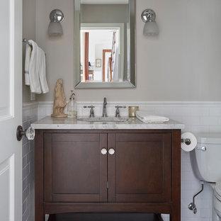 Inspiration pour un petit WC et toilettes traditionnel avec un placard à porte shaker, des portes de placard en bois sombre, un WC à poser, un carrelage blanc, un carrelage métro, un mur gris, un lavabo posé, un sol gris, un sol en carrelage de porcelaine et un plan de toilette en quartz.