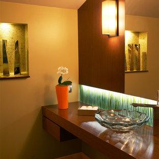 Modelo de aseo pequeño con lavabo sobreencimera, armarios con paneles lisos, puertas de armario de madera en tonos medios, encimera de madera, sanitario de una pieza, baldosas y/o azulejos verdes, baldosas y/o azulejos de vidrio laminado, paredes amarillas y encimeras marrones