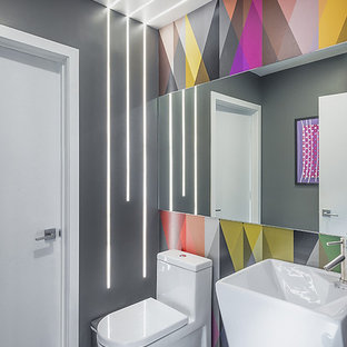 Inspiration for a contemporary medium tone wood floor and brown floor powder room remodel in Los Angeles with multicolored walls and a pedestal sink