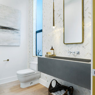 Inspiration for a large contemporary white tile and marble tile light wood floor powder room remodel in Los Angeles with a one-piece toilet, white walls, a trough sink and concrete countertops
