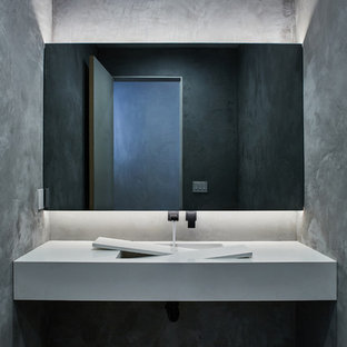 Example of a minimalist gray floor powder room design in Los Angeles with gray walls and white countertops