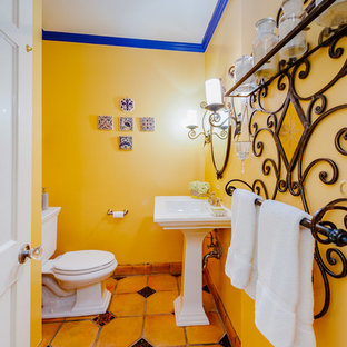 Design ideas for a small mediterranean cloakroom in Los Angeles with a two-piece toilet, yellow walls, a pedestal sink and yellow floors.