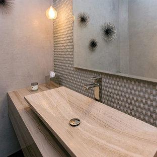 ロサンゼルスの中くらいのコンテンポラリースタイルのおしゃれなトイレ・洗面所 (フラットパネル扉のキャビネット、グレーのキャビネット、一体型トイレ、ベージュのタイル、ガラスタイル、ベージュの壁、濃色無垢フローリング、ベッセル式洗面器、トラバーチンの洗面台、茶色い床、ベージュのカウンター) の写真