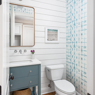 Inspiration for a large transitional brown floor and medium tone wood floor powder room remodel in Chicago with flat-panel cabinets, white walls, white countertops, blue cabinets, a two-piece toilet and a console sink
