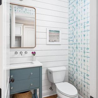 Inredning av ett klassiskt stort vit vitt toalett, med släta luckor, vita väggar, brunt golv, blå skåp, en toalettstol med separat cisternkåpa, mellanmörkt trägolv och ett konsol handfat