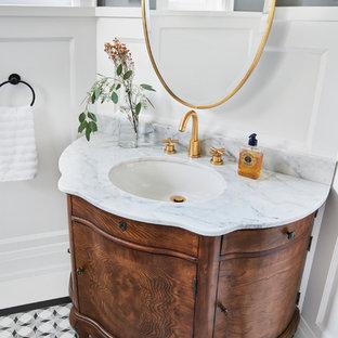 Exemple d'un WC et toilettes chic de taille moyenne avec un placard en trompe-l'oeil, des portes de placard marrons, un WC à poser, un carrelage gris, un sol en carrelage de terre cuite, un lavabo encastré, un plan de toilette en marbre et un sol blanc.