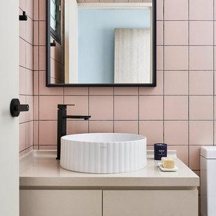 Moderne Gästetoilette mit flächenbündigen Schrankfronten, beigen Schränken, rosafarbenen Fliesen, rosa Wandfarbe, Aufsatzwaschbecken und beiger Waschtischplatte in Singapur
