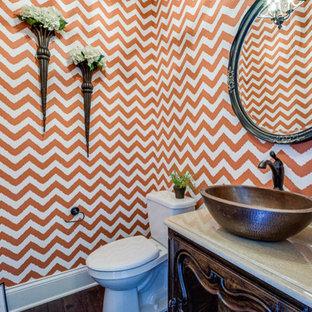 Immagine di un piccolo bagno di servizio country con consolle stile comò, ante in legno bruno, WC a due pezzi, pareti arancioni, parquet scuro, lavabo a bacinella e top in superficie solida